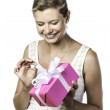 Young pretty woman unwraps gift — Stock Photo