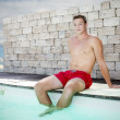 Handsome man sitting on pool — Stock Photo #32469489