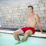 Handsome man sitting on pool — Stock Photo #32469489