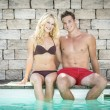 Blond girl and handsome boy on swimming pool — Stock Photo
