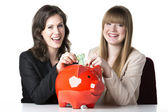 Two women with piggy bank — Stok fotoğraf