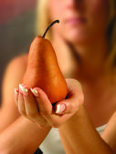 Young woman holding pear — Stock Photo