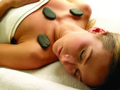 Woman receiving a therapy with hot stones in spa salon — Stock Photo