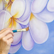 A female artist painting flowers — Stock Photo