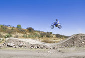 A picture of a biker making a stunt and jumps in the air — Stock Photo