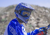 Föraren går sluttande lämnar ett spår av damm med sin motocross cykel — Stockfoto
