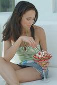 Beautiful woman enjoying fruit dessert with icecream — Stock Photo