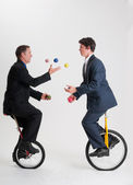 Juggling businessmen riding unicycles — Stock Photo