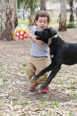 Boy and untrained dog fight over ball — Foto de Stock
