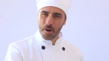 Bearded middle-aged chef in white toque and uniform standing looking at the camera with copyspace on white — Stock Video