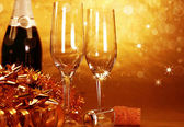 Champagne glasses on golden background — Stock Photo
