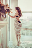 Beautiful woman near window — Stock Photo
