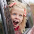 Portrait of a surprised girl in a car - Stock Photo