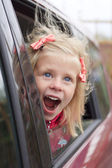 Portrait of a surprised girl in a car — Stock Photo