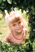 Рortrait of a smiling girl in a frame of green leaves — Stock Photo