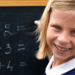 Schoolgirl at the blackboard — Stock Photo #28114481