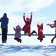 Group of cheerful children jumping in winter — Stock Photo