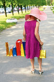 Little elegant girl walking down the street with shopping bags — Stock Photo