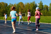 Group of children running around the stadium in the summer — Stock Photo