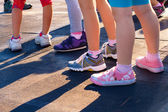Group of children's feet in sneakers — Stock Photo