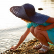 Little girl sitting near the water — Stock Photo