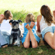 Girl lying on the grass with a dog — Stockfoto