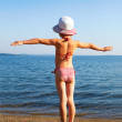 Stock Photo: Girl standing on beach in striped bathing suit