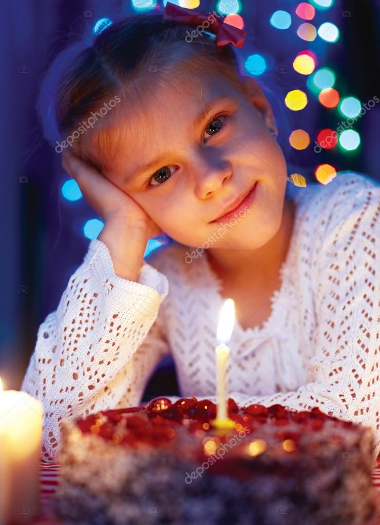 可爱的小女孩看着一支蜡烛的蛋糕