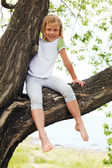 Cute girl sitting on a tree in summer — Stock Photo