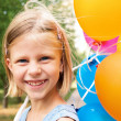 Smiling girl with balloons — Stock Photo