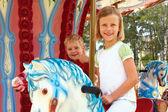 Мальчик и девочка катаются на карусели — Стоковое фото