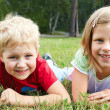 Boy and girl lying on green grass — Stock Photo