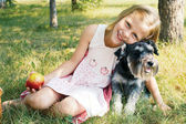 Laughing little girl hugging her dog — Stock Photo