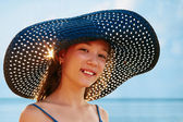 Girl in a hat on a background of ocean — Stok fotoğraf