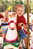 Curly little boy riding a carousel  — Stockfoto