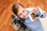 Girl photographing herself and her dog — Stock Photo