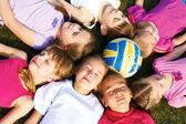Bir daire içinde yerde yatan çocuklar mutlu grup — Stok fotoğraf