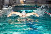 Homem nada no nado de borboleta de natação piscina — Fotografia Stock