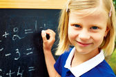 Schoolgirl decides on a blackboard mathematical tasks — Stok fotoğraf