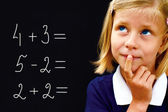 Schoolgirl doing arithmetic on blackboard in class and smiling  — Stock Photo