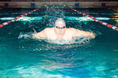 Man swims in the swim pool butterfly stroke — Stockfoto