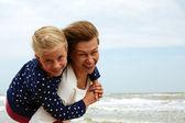 Familia feliz descansando en la playa en verano — Foto de Stock