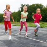 Three  girls run down around the stadium — Stock Photo #51586629