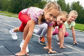 girls starting to run on track — Stock Photo