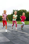 Three  girls run down around the stadium — Stock Photo