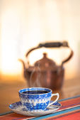 Blue coffee cup with a copper kettle in background — Stock Photo