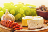 Brie cheese with olives, grapes and chorizo — Stock Photo