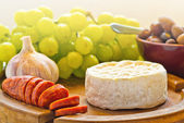Brie cheese with olives and chorizo — Stock Photo
