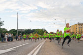 STOCKHOLM - AUG, 17: Just after the start in one of many groups for children in the Midnight Run for children (Lilla Midnattsloppet) event, a group of excited children running — Foto de Stock