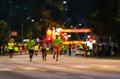 STOCKHOLM - AUG, 17: Just before the start of the Midnight Run (Midnattsloppet) event, three men warming up, the start in visible in blurred background. Aug 17, 2013 in Stockholm, Sweden — Stock Photo